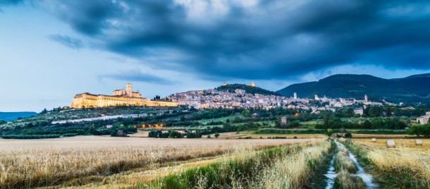 Beautiful view of Assisi with dramatic cloudscape during blue hour, Umbria, Italy