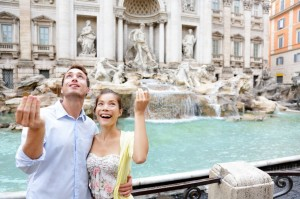 Honeymooners trowing coin at Trevi Fountain in Rome, Italy